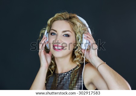 Woman with headphones on, touching the earcups