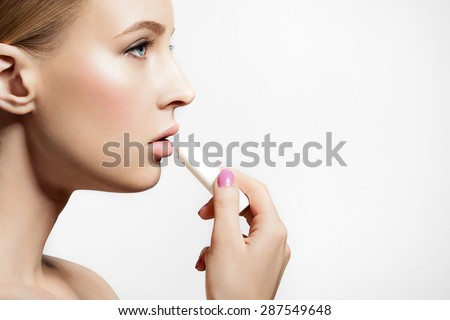 Woman with healthy skin applying a protective lip balm n a white background - stock photo