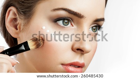 woman with healthy skin applying cream highlighter under eye - stock photo
