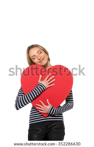 Woman with heart - Young beautiful Caucasian woman holding a big red heart in her arms - stock photo