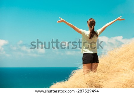 Woman with her arms outstretched enjoying the ocean breeze. - stock photo