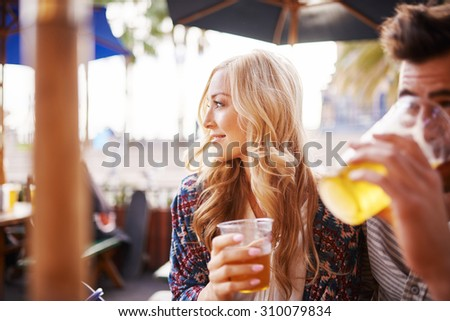 woman with her boyfriend enjoying drinking a beer at outdoor beach side bar or pub - stock photo