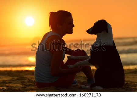 Woman with her cute dog in the beach on golden sunset background. Girl enjoying her pet friendship and affection towards beautiful sun and sea. - stock photo