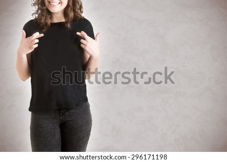 Woman with her fingers crossed for good luck, isolated in grey - stock photo
