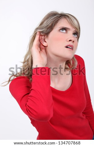 Woman with her hand to her ear - stock photo