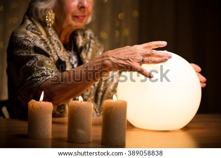Woman with her hands on lighted crystal ball - stock photo