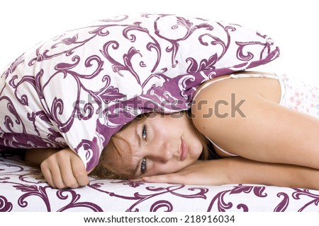 Woman with her head under her pillow trying to sleep. - stock photo