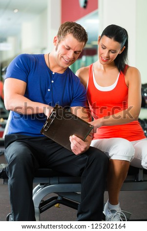 Woman with her personal fitness trainer in the gym exercising with dumbbells - stock photo