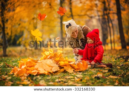 woman with her son preparing food on autumn leaves fire - stock photo