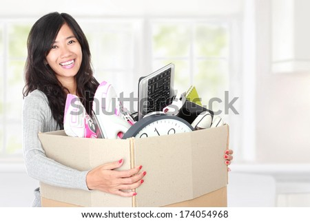 woman with her stuff inside the cardboard box ready to move. moving day concept - stock photo