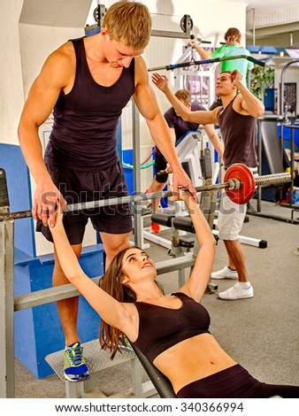 Woman with her trainer  working dumbbells his body at gym.  - stock photo
