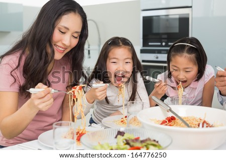 Woman with her two happy kids enjoying spaghetti lunch in the kitchen at home - stock photo