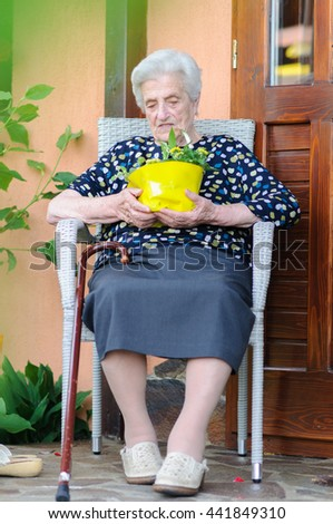 Woman with her walking stick sitting outside