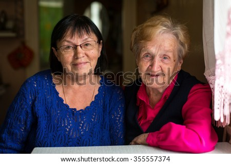 Woman with his old mother, a close-up portrait. - stock photo