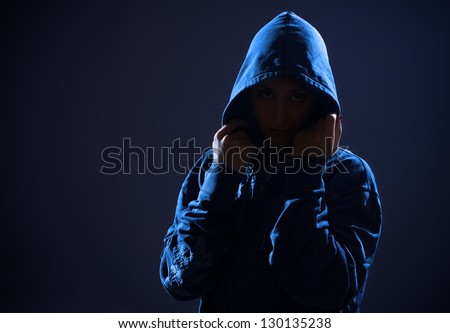 woman with hood in darkness - stock photo