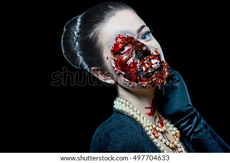Woman with horror make up in the studio on a black background. Halloween make up. Audrey Hepburn style