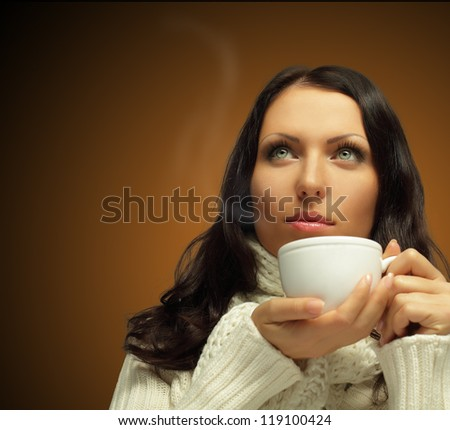 Woman with hot coffee on dark brown background - stock photo