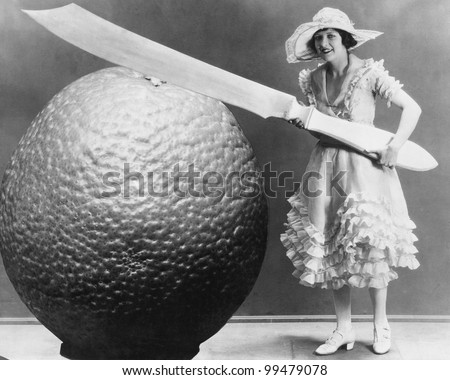 Woman with huge knife and piece of fruit - stock photo