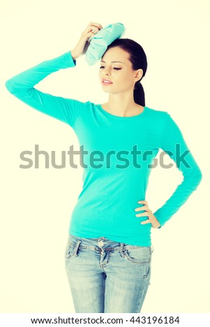 Woman with ice bag for headaches and migraines - stock photo