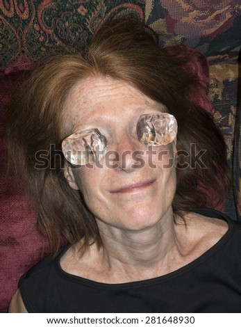 woman with ice cubes on eyes - stock photo