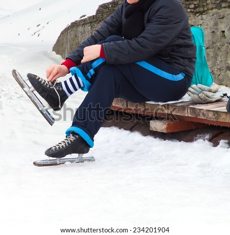 woman with ice skates on winter ice - stock photo