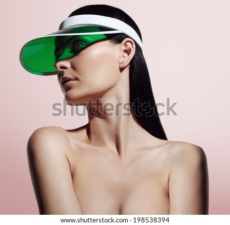 woman with ideal skin in green gel cap on the pink background - stock photo