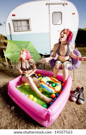 Woman with in an inflatable play pool playing with bubbles