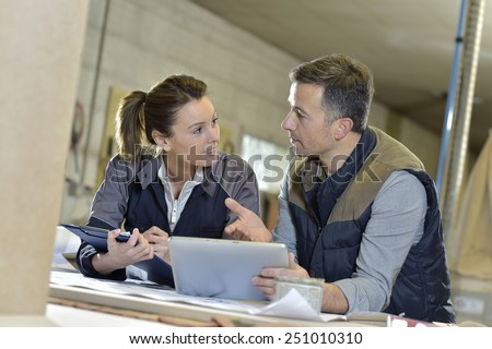Woman with instructor in carpentry workshop - stock photo