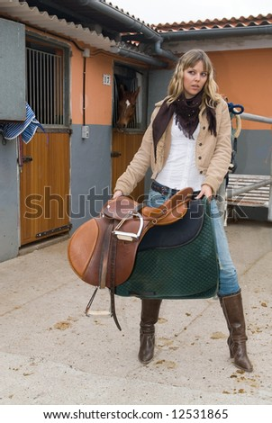Woman with jeans and boots in an stable - stock photo