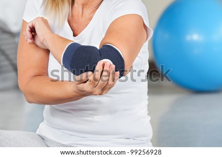 Woman with joint pain and bandage in gym - stock photo