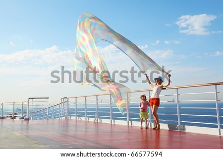 woman with kerchief standing on deck of cruise ship. her daughter looking at kerchief