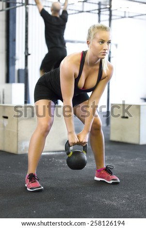 Woman with kettlebell at the fitness gym - stock photo