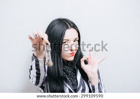 Woman with keys showing okay. On a gray background. - stock photo