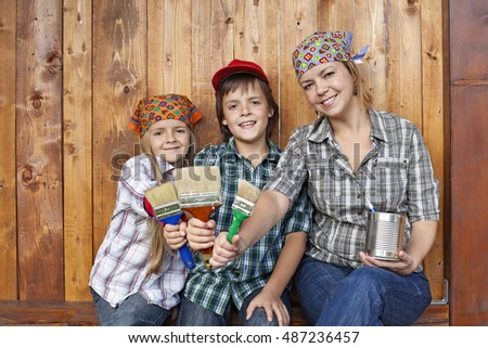Woman with kids ready to paint the shed together
