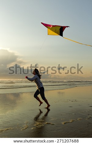 Woman with kite at beach in Newport, Oregon. - stock photo