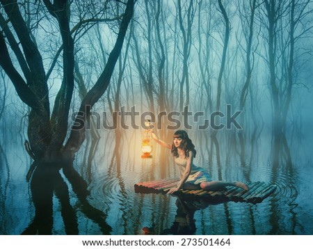 Woman with lantern floating on the lake in the misty forest in rustic dress. Beautiful fairy tale.