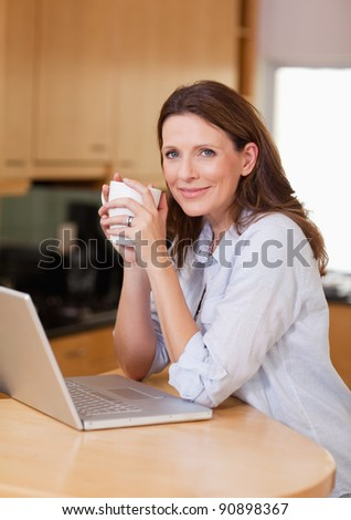 Woman with laptop and a cup in the kitchen - stock photo