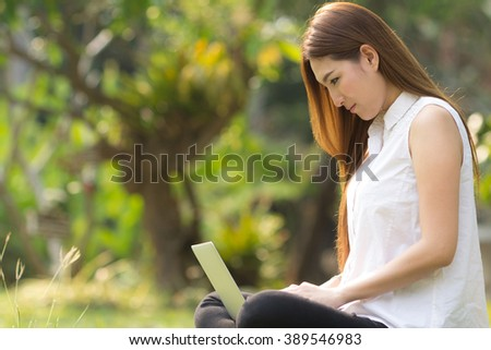 woman with laptop. asian beautiful young woman with notebook sitting on the grass.