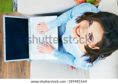 Woman with laptop looking up. Working at home. - stock photo