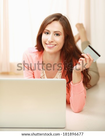 Woman with laptop lying down on the floor and holding a credit card