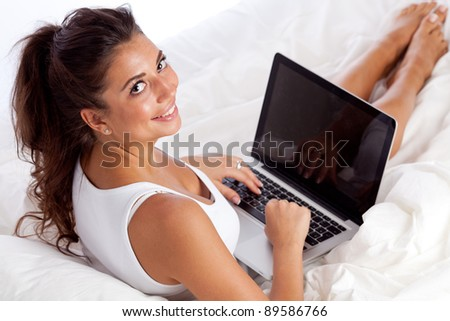 Woman with laptop lying in bed