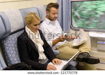 Woman with laptop man newspaper in train texting commuting reading - stock photo