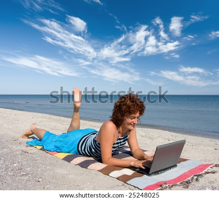 woman with laptop on the sand sea beach