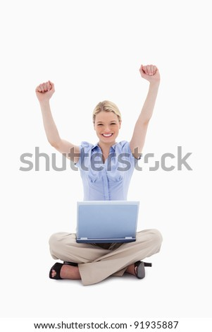 Woman with laptop raising her hands against a white background - stock photo
