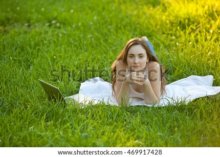 Woman with laptop relaxing lying on green grass