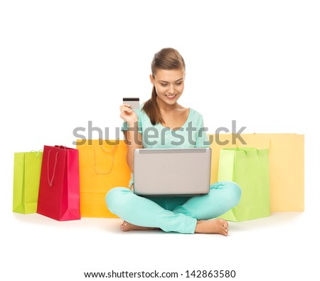 woman with laptop, shopping bags and credit card - stock photo