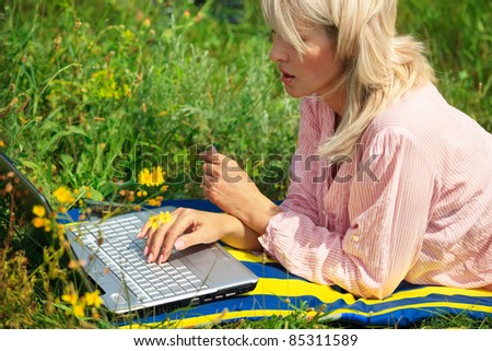 Woman with laptop sitting on field - stock photo