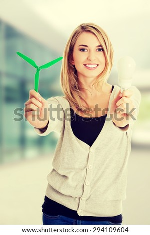 Woman with led light bulb and windmill. - stock photo