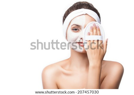 Woman with lifting cream applied on a half of her face, isolated on white - stock photo