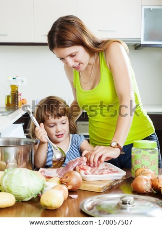 woman with little girl cooking at home kitchen
